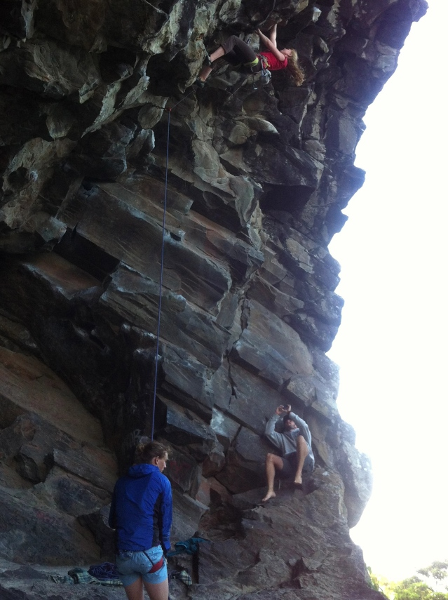 "Stefanie Wolf climbs ""Does it have a chevy motor"", 23. While Abe Burford belays and Nick Foster snaps a photo."